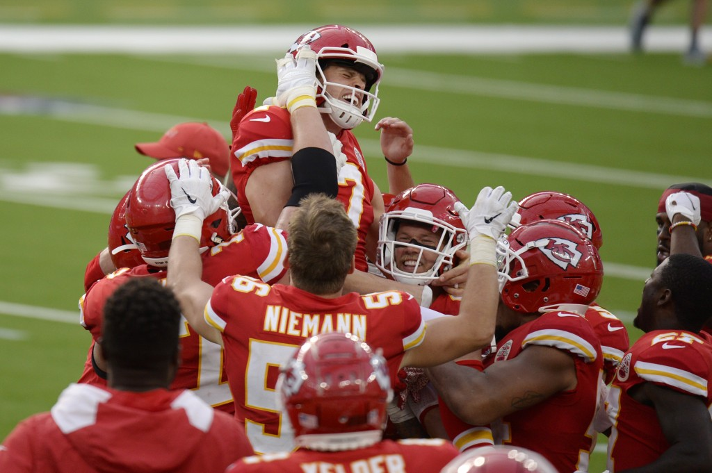 Kansas City Chiefs kicker Harrison Butker, top, is lifted by teammates after making the game-winning field goal during overtime of an NFL football gam...