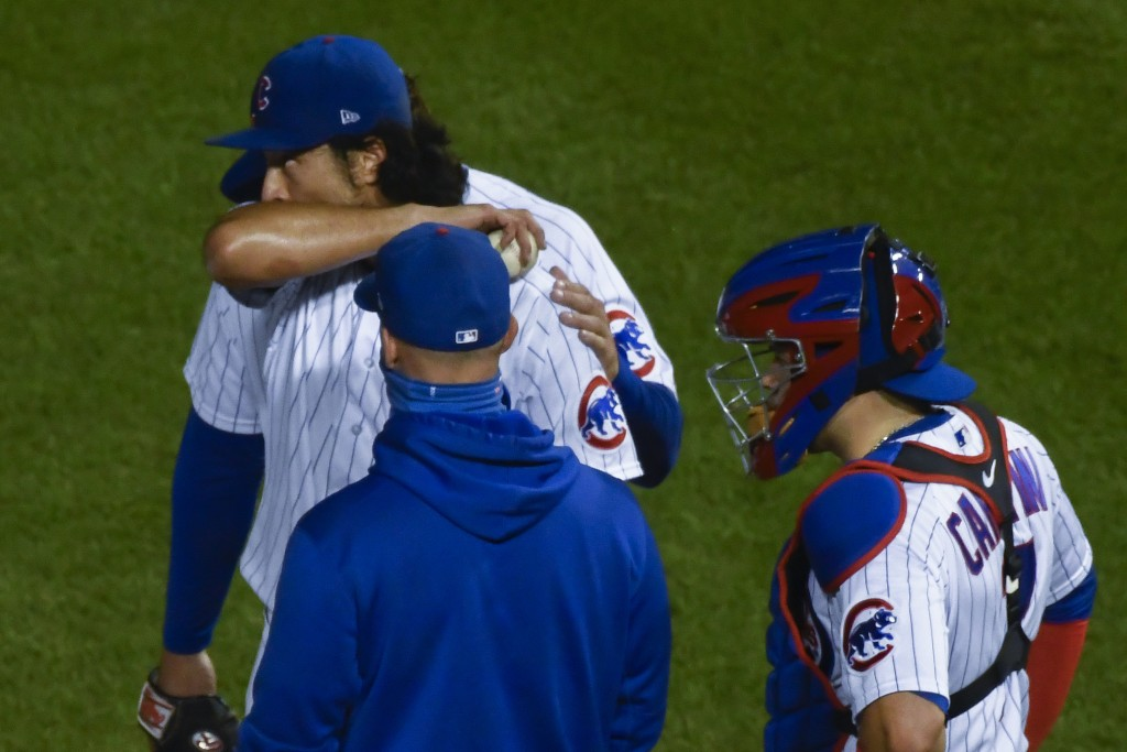 Chicago Cubs starting pitcher Yu Darvish, center, is patted on the back by first baseman Anthony Rizzo, back, after being relieved during the seventh ...