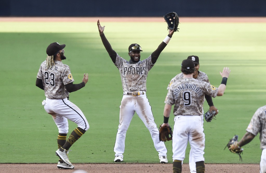 San Diego Padres' Fernando Tatis Jr. (23), Jurickson Profar (10), and Jake Cronenworth (9) celebrate after the Padres beat the Seattle Mariners in a b...