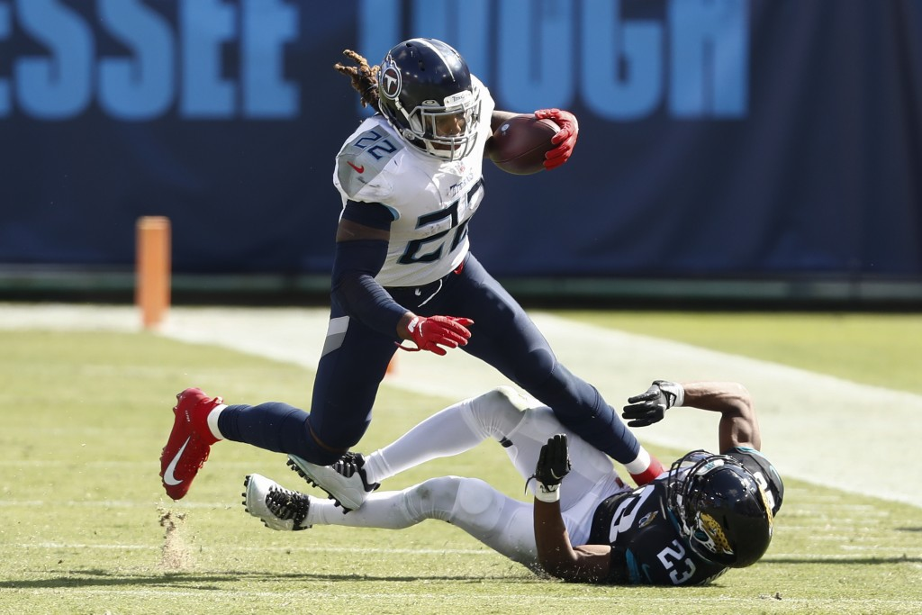 Tennessee Titans running back Derrick Henry (22) runs past Jacksonville Jaguars cornerback C.J. Henderson (23) in the second half of an NFL football g...