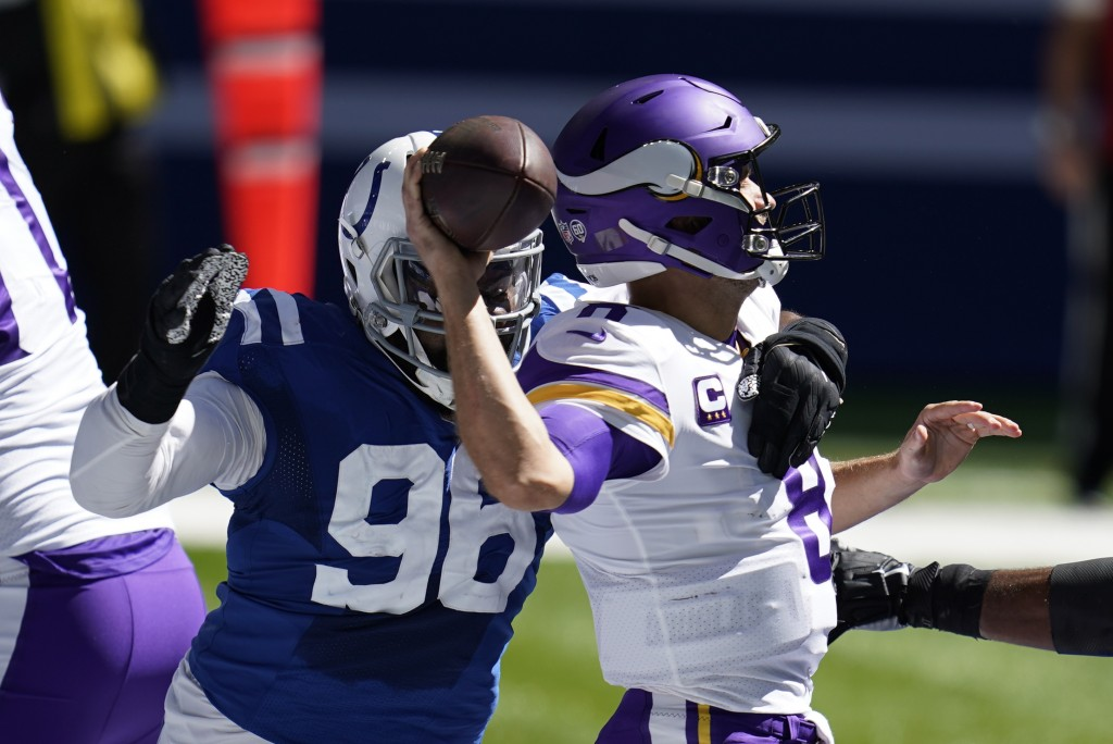 Minnesota Vikings quarterback Kirk Cousins, right, is pressured by dIndianapolis Colts' Denico Autry (96) during the first half of an NFL football gam...