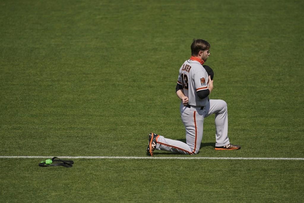 San Francisco Giants' Austin Slater kneels during the national anthem before a baseball game against the Oakland Athletics in Oakland, Calif., Sunday,...