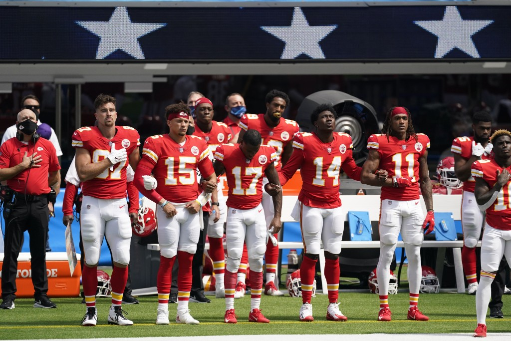Kansas City Chiefs player lock arms as the national anthem plays before an NFL football game against the Los Angeles Chargers Sunday, Sept. 20, 2020, ...