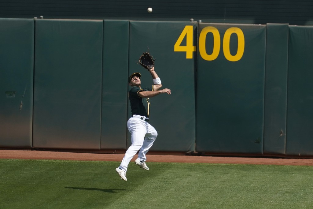 Oakland Athletics center fielder Ramon Laureano catches a ball hit by San Francisco Giants' Brandon Belt for an out during the first inning of a baseb...