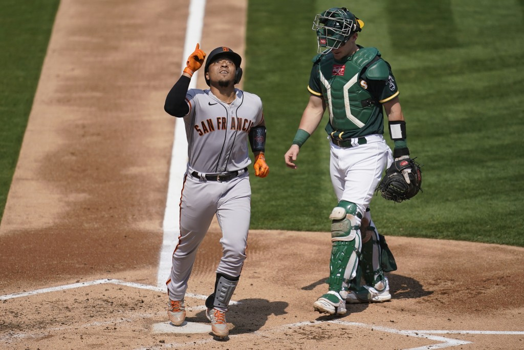 San Francisco Giants' Chadwick Tromp, left, celebrates after hitting a two-run home run next to Oakland Athletics catcher Sean Murphy during the third...