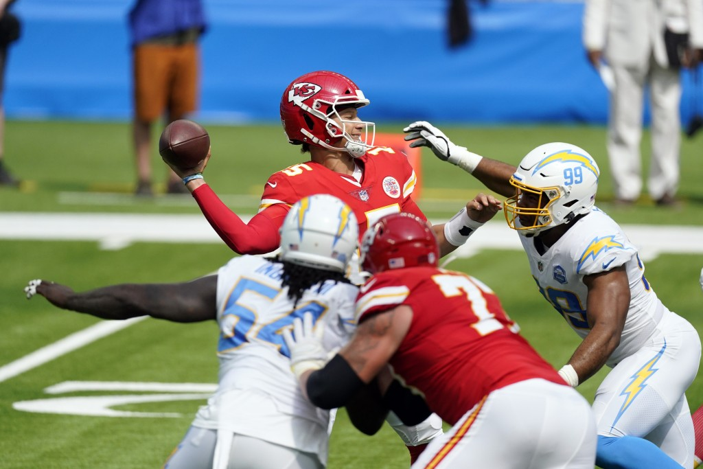 Kansas City Chiefs quarterback Patrick Mahomes throws under pressure agains the Los Angeles Chargers during the first half of an NFL football game Sun...