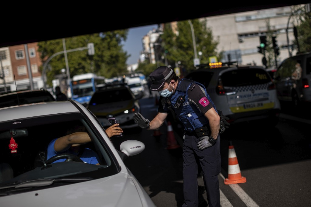 A local police stops a vehicle at a checkpoint in Madrid, Spain, Monday, Sept. 21, 2020. Police in the Spanish capital and its surrounding towns are s...