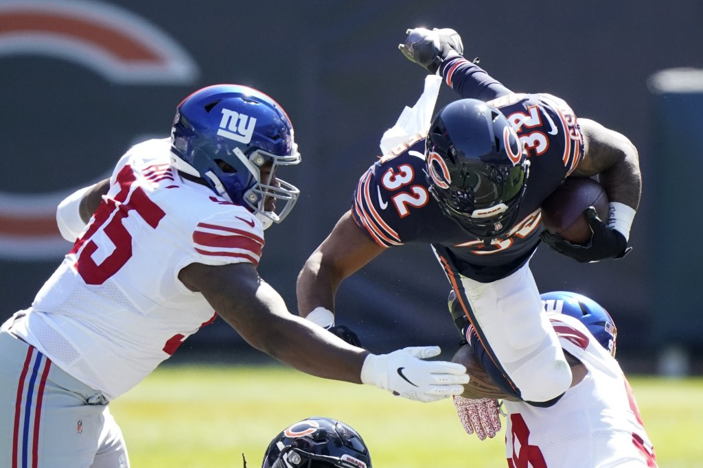 Chicago Bears running back David Montgomery (32) is brought down by New York Giants nose tackle Austin Johnson (98) as defensive end B.J. Hill (95) as...