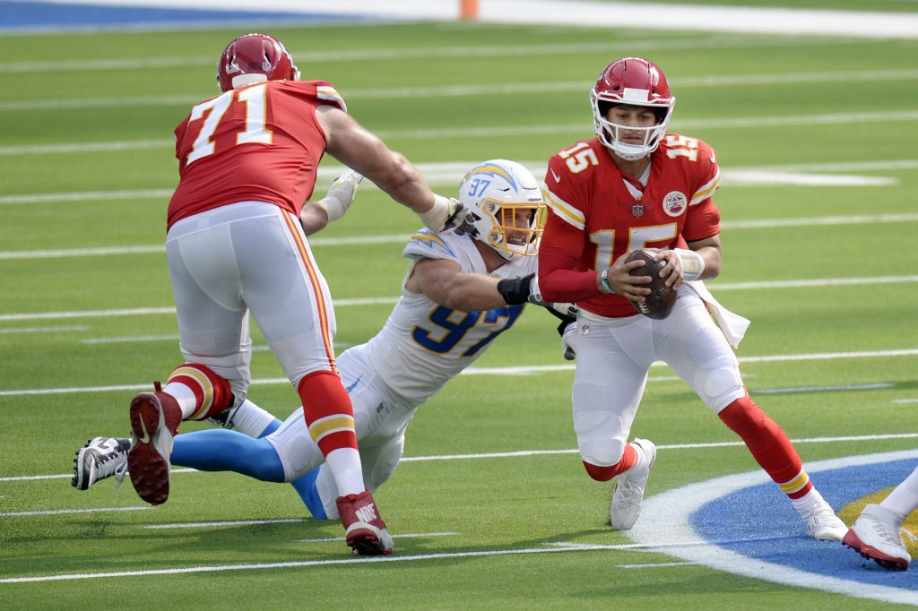 Kansas City Chiefs quarterback Patrick Mahomes, right, is tackled by Los Angeles Chargers defensive end Joey Bosa, center, during the second half of a...