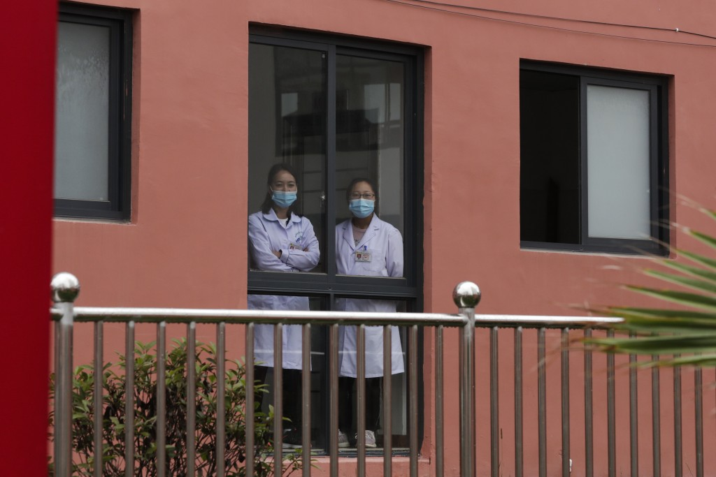 Medical workers look out from a healthcare center at the apartment houses compound built by the Chinese government in Yuexi county, southwest China's ...