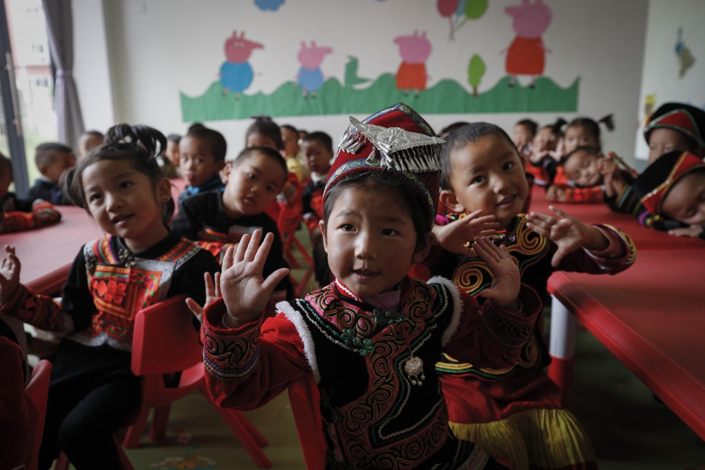 Ethnic minority children wearing their costumes learn to sing at a kindergarten class at the apartment houses compound built by the Chinese government...