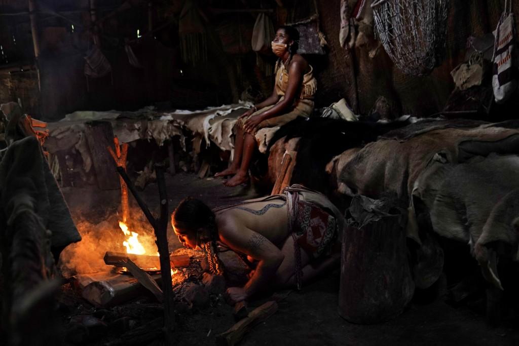 Tatanka Gibson, kneeling, a member of the Haliwa band of Nansemond and Saponi and a museum educator at Plimoth Plantation, a reconstructed living hist...