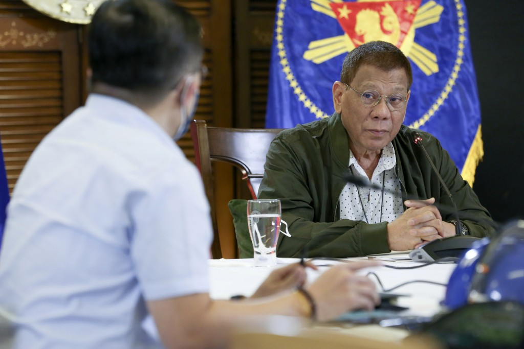 In this photo provided by the Malacanang Presidential Photographers Division, Philippine President Rodrigo Duterte, right, listens as he meets members...