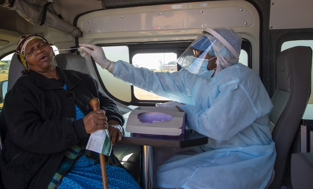 FILE - In this May 22, 2020, file photo, an elderly woman reacts as a heath worker collects a sample during the screening and testing campaign aimed t...
