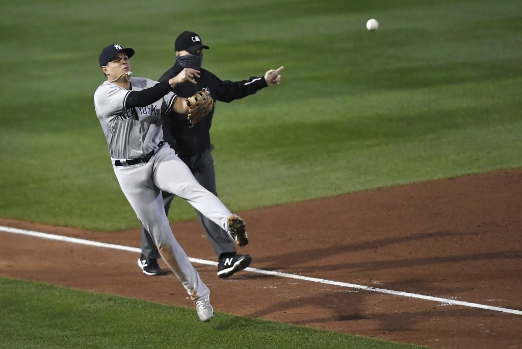 New York Yankees third baseman Gio Urshela, left, throws home after fielding a ground ball by Toronto Blue Jays' Teoscar Hernandez during the fourth i...