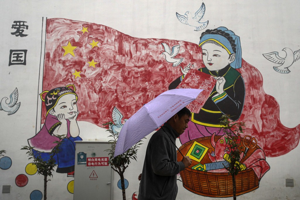 A man holding an umbrella walks by a new village house decorated with a patriotic painting which was built by the Chinese government for ethnic minori...