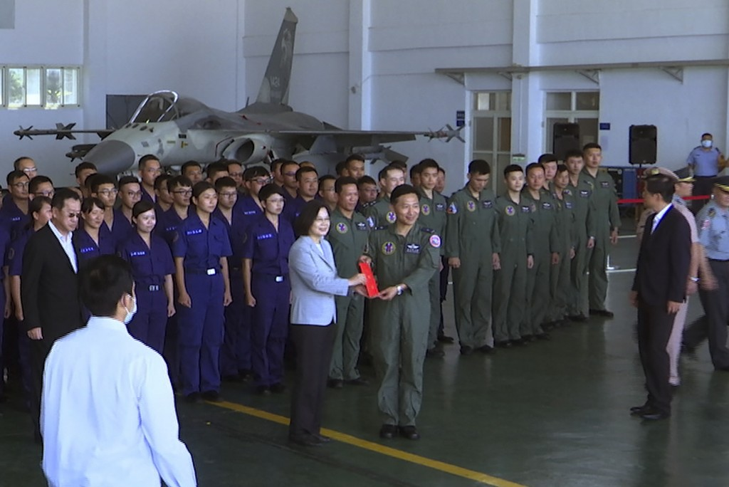 Taiwan President Tsai Ing-wen, center left, poses for photos with airmen near a Taiwan Indigenous Defense Fighter (IDF) jet displayed during a visit t...