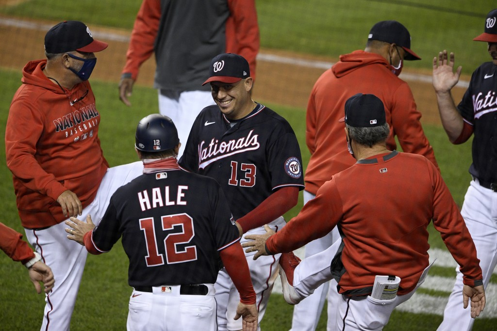 Washington Nationals' Asdrubal Cabrera (13) celebrates with third base coach Chip Hale (12) and others after a baseball game against the Philadelphia ...