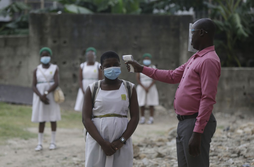FILE - In this Aug. 4, 2020, file photo, a teacher checks students for fever at Lagos State Model School in Lagos, Nigeria. The coronavirus pandemic h...