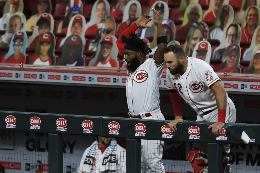 Cincinnati Reds' Brian Goodwin, left, and Curt Casali, right, react to the two-run home run hit by Eugenio Suarez in the sixth inning during a basebal...