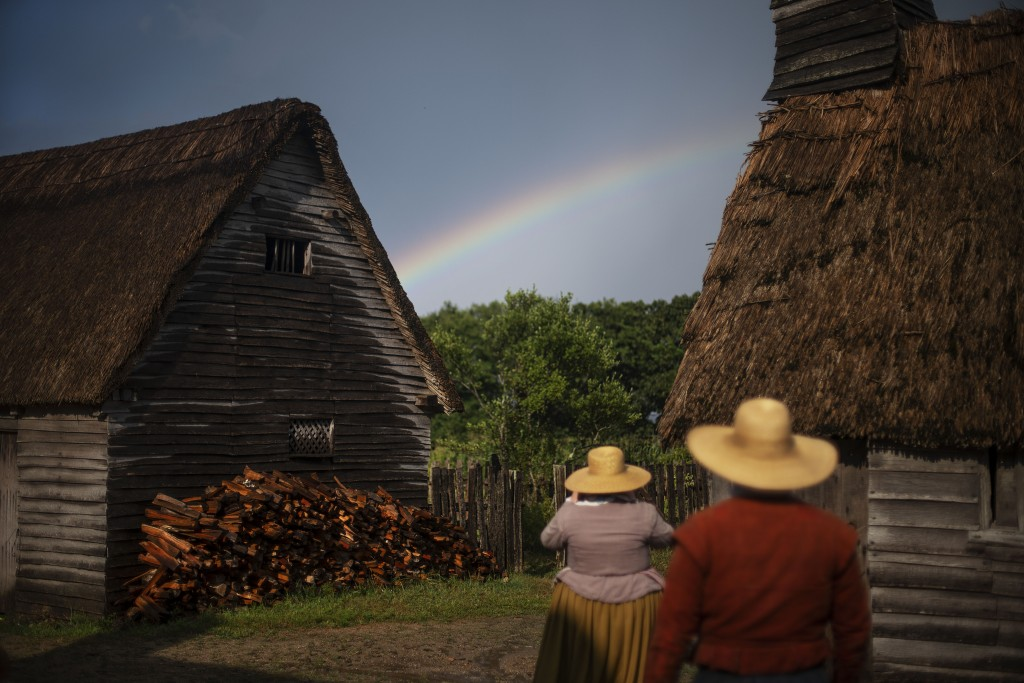 Museum educators playing the role of Pilgrims look at a rainbow over Plimoth Plantation, a living history museum village, Wednesday, Aug. 12, 2020, in...