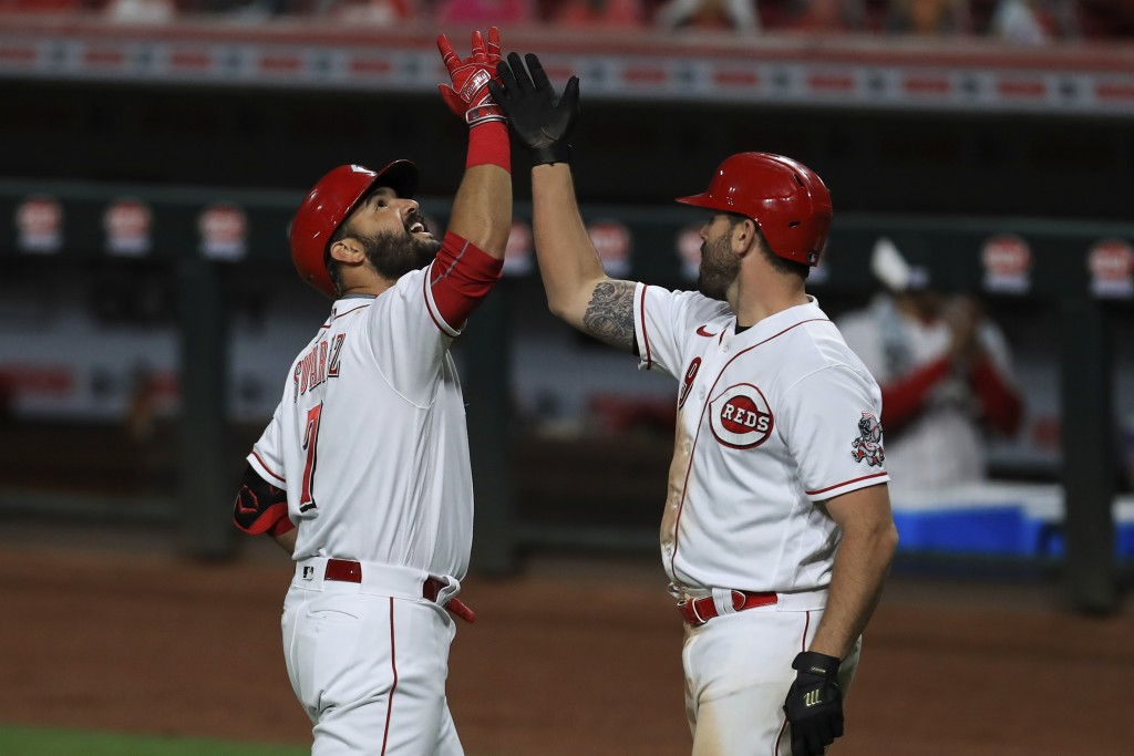 Cincinnati Reds' Eugenio Suarez, left, celebrates after hitting a two-run home run with teammate Mike Moustakas, right, in the sixth inning during a b...