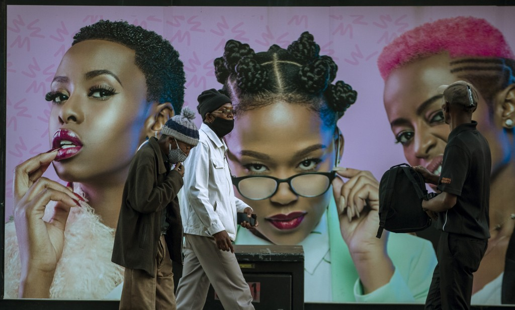 FILE - In this Monday, June 29, 2020, file photo, men in face masks walk past a hair product billboard on the street in Soweto, South Africa. The coro...