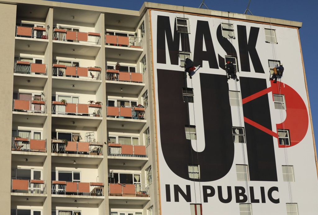 FILE - In this May 16, 2020, file photo, a billboard is installed on an apartment building encouraging people to wear face masks in Cape Town, South A...