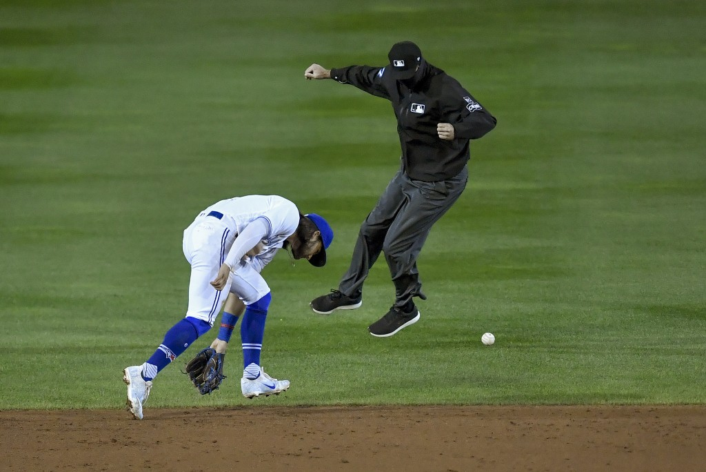 The second base umpire, right, avoids the ball as Toronto Blue Jays shortstop Bo Bichette, left, cannot get to a single hit by New York Yankees' Gio U...