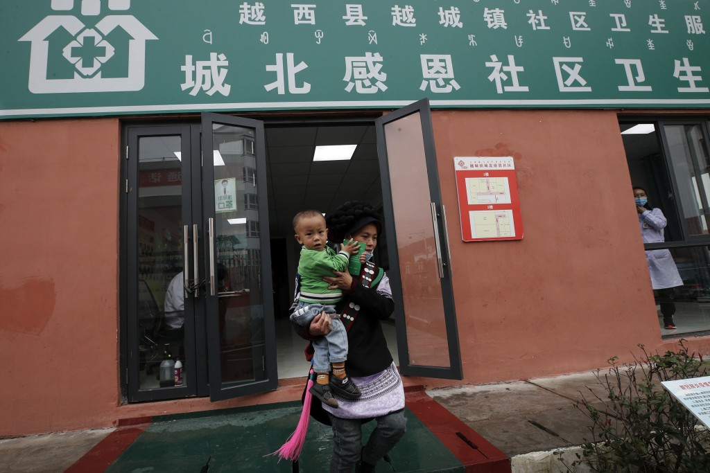 An ethnic minority woman carrying her child leaves a clinic at the apartment houses compound built by the Chinese government in Yuexi county, southwes...