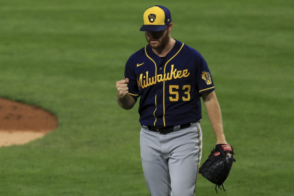 Milwaukee Brewers' Brandon Woodruff reacts to an inning-ending double play hit into by Cincinnati Reds' Jesse Winker in the fourth inning during a bas...