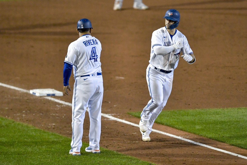 Toronto Blue Jays' Randal Grichuk, right, celebrates with third base coach Luis Rivera, left, after hitting a solo home run against the New York Yanke...
