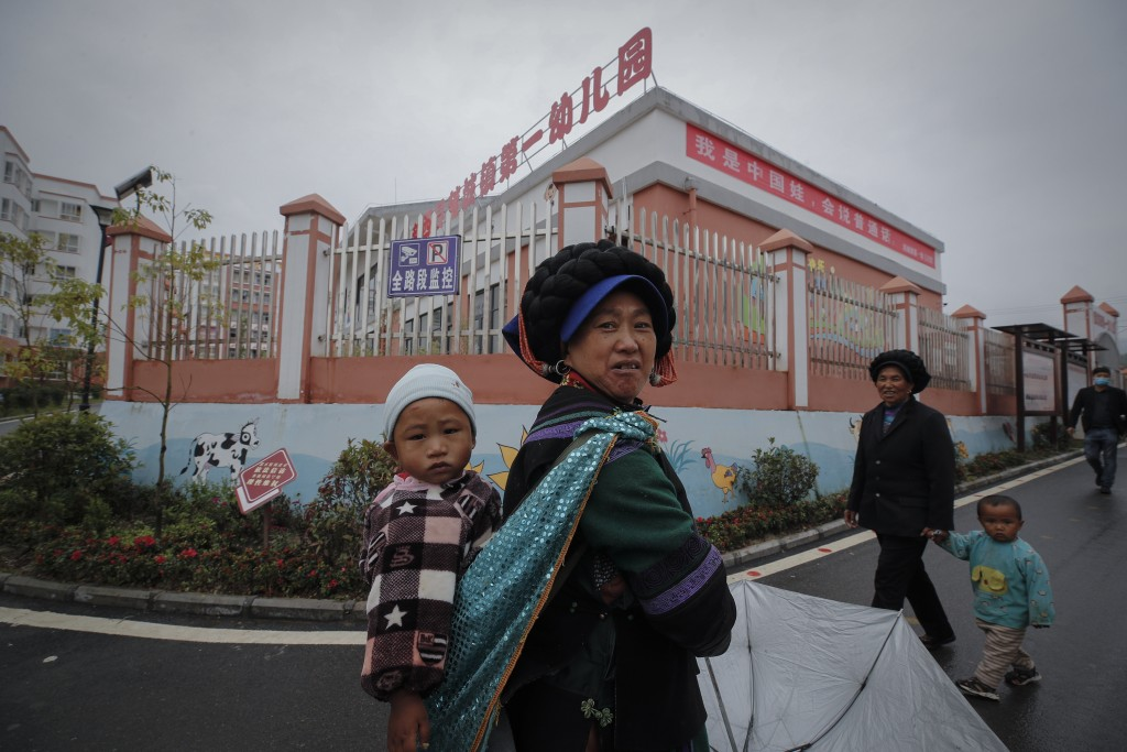 "Ethnic minority women walk with their child near a kindergarten with a banner which reads ""I'm a China doll, can speak Mandarin"" at the apartment hous..."