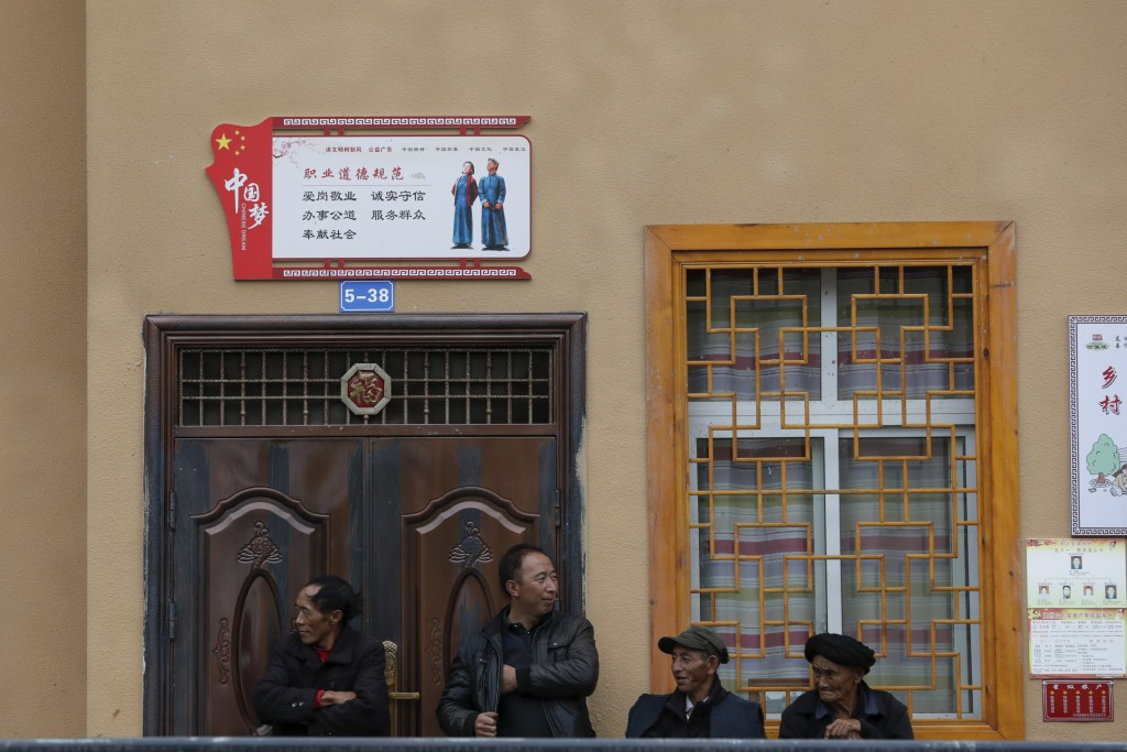 Ethnic monitory residents take a rest outside a new village house decorated with China's propaganda slogan in Ganluo county, southwest China's Sichuan...
