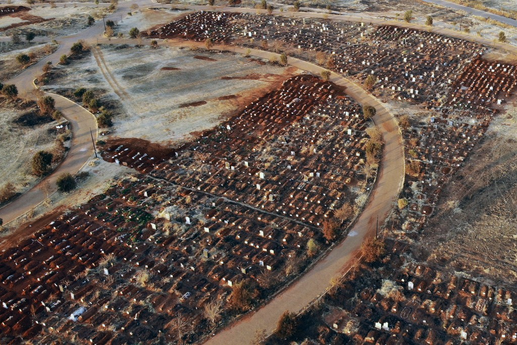 FILE - In this Aug. 5, 2020, file photo, fresh graves fill the Olifantsveil Cemetery outside Johannesburg, South Africa. The coronavirus pandemic has ...
