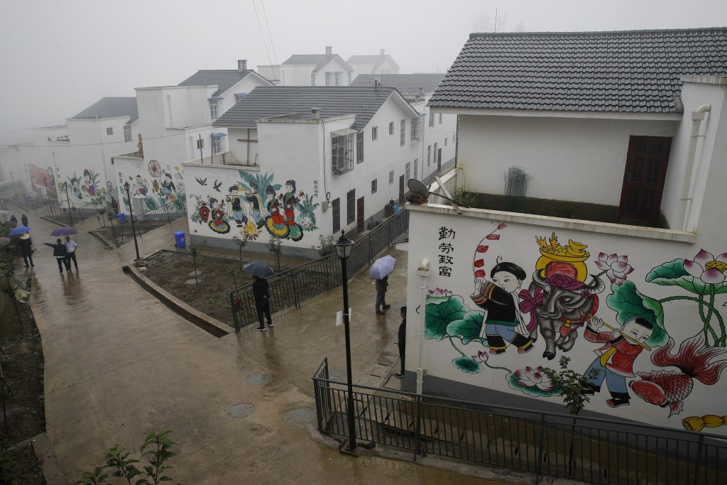 People walk by new village houses decorated with colourful paintings built by the Chinese government for ethnic minority members in Ganluo county, sou...