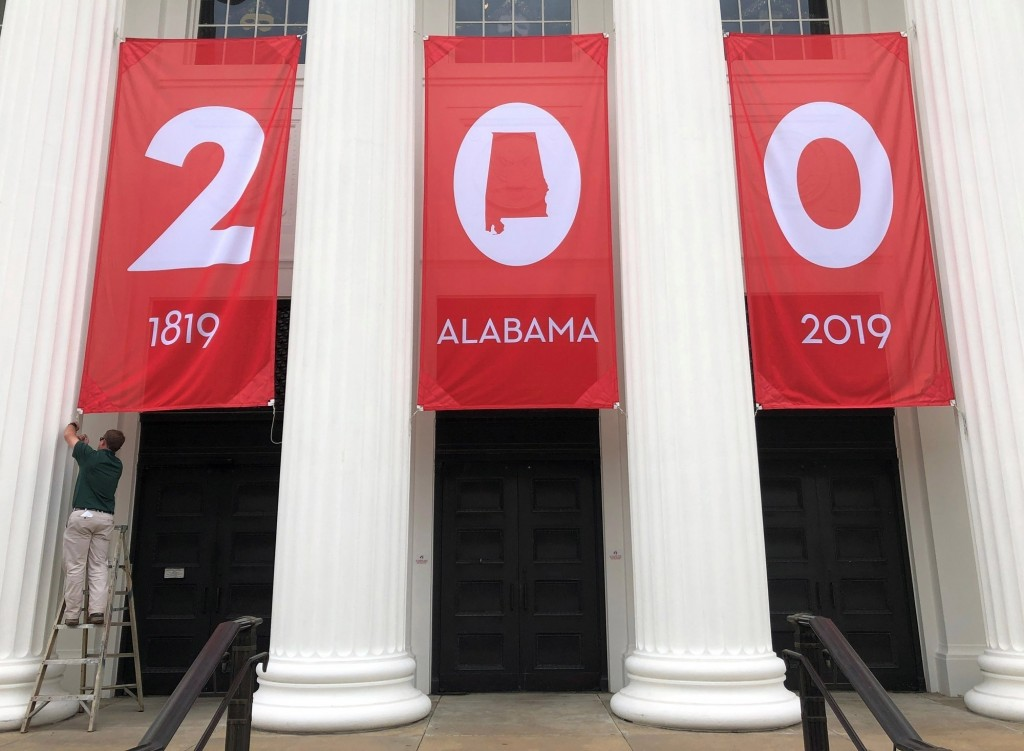 FILE - In this Feb. 28, 2019 file photo a worker adjusts a banner celebrating Alabama's bicentennial outside the Department of Archives and History in...