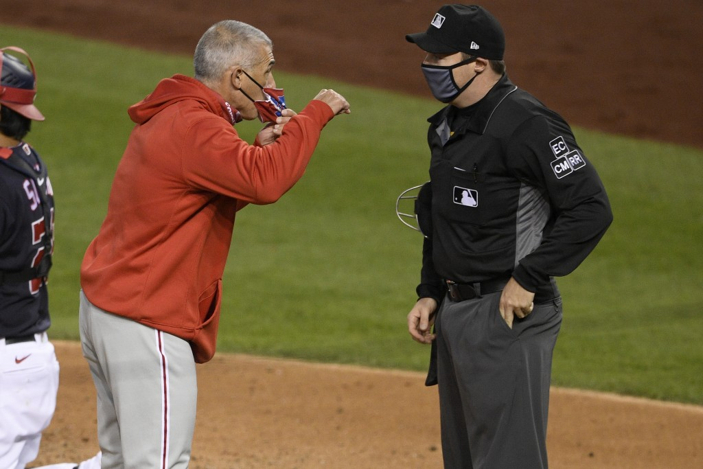 Philadelphia Phillies manager Joe Girardi, left, argues with home plate umpire Junior Valentine, right, after he was ejected during the third inning o...