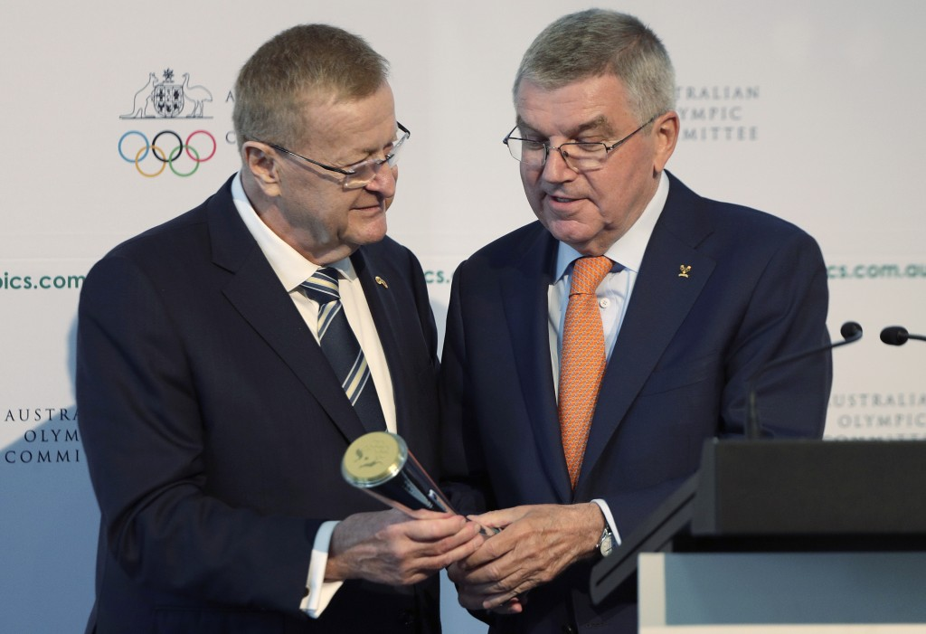 FILE - In this May 4, 2019, file photo, International Olympic Committee President Thomas Bach, right, is presented with the Australian Olympic Committ...