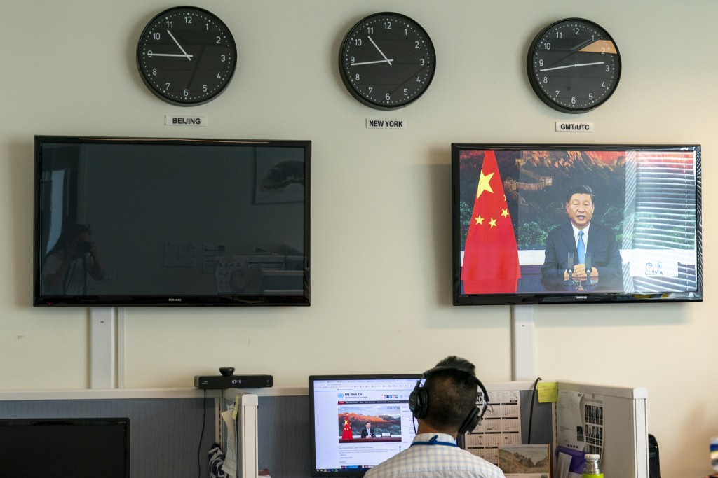A reporter with the Xinhua Press Agency watches as President Xi Jinping is seen on a video screen remotely addressing the 75th session of the United N...