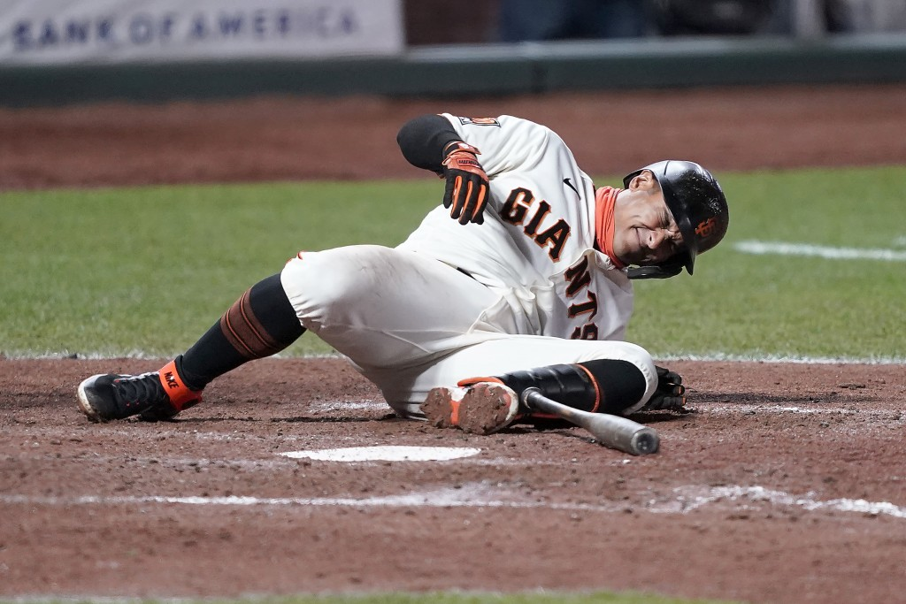 San Francisco Giants' Donovan Solano grimaces after being hit by a pitch against the Colorado Rockies during the seventh inning of a baseball game on ...