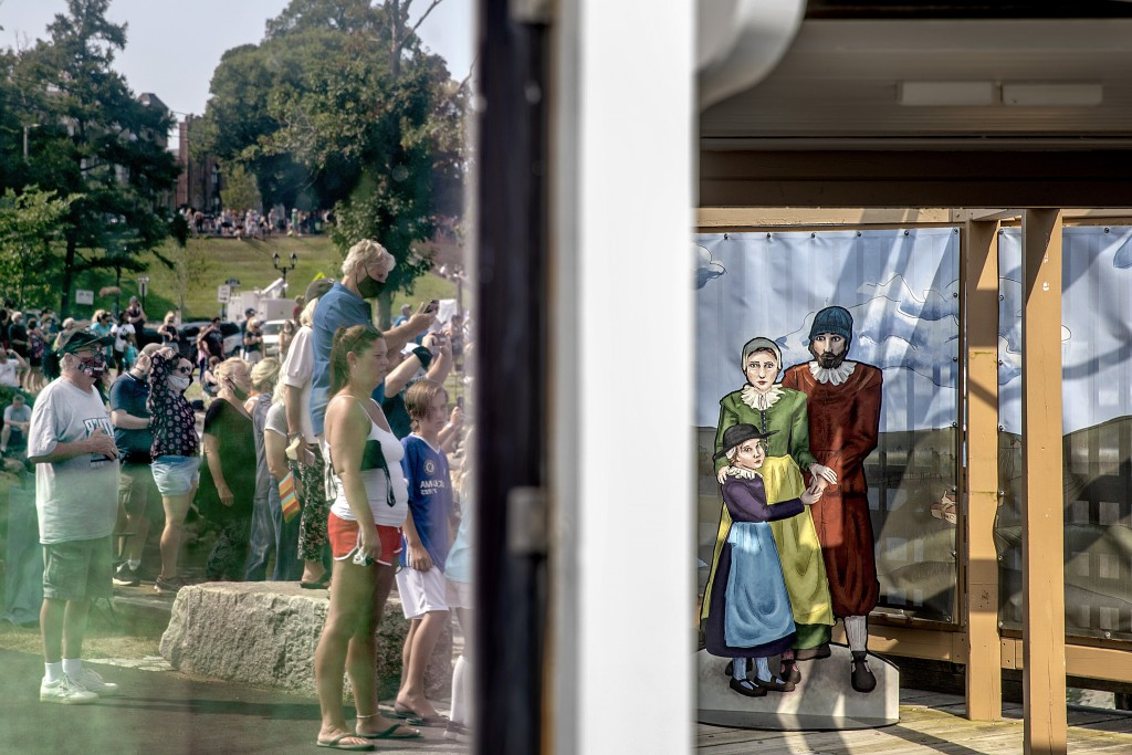 A crowd is reflected in the window of a ticket booth next to a cutout, right, of Pilgrims as they wait for the Mayflower II, a replica of the original...