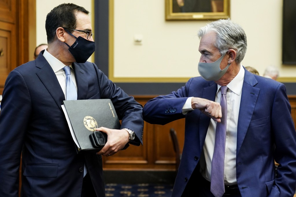 Treasury Secretary Steven Mnuchin, left, greets Federal Reserve Chair Jerome Powell with an elbow bump before the start of a House Financial Services ...