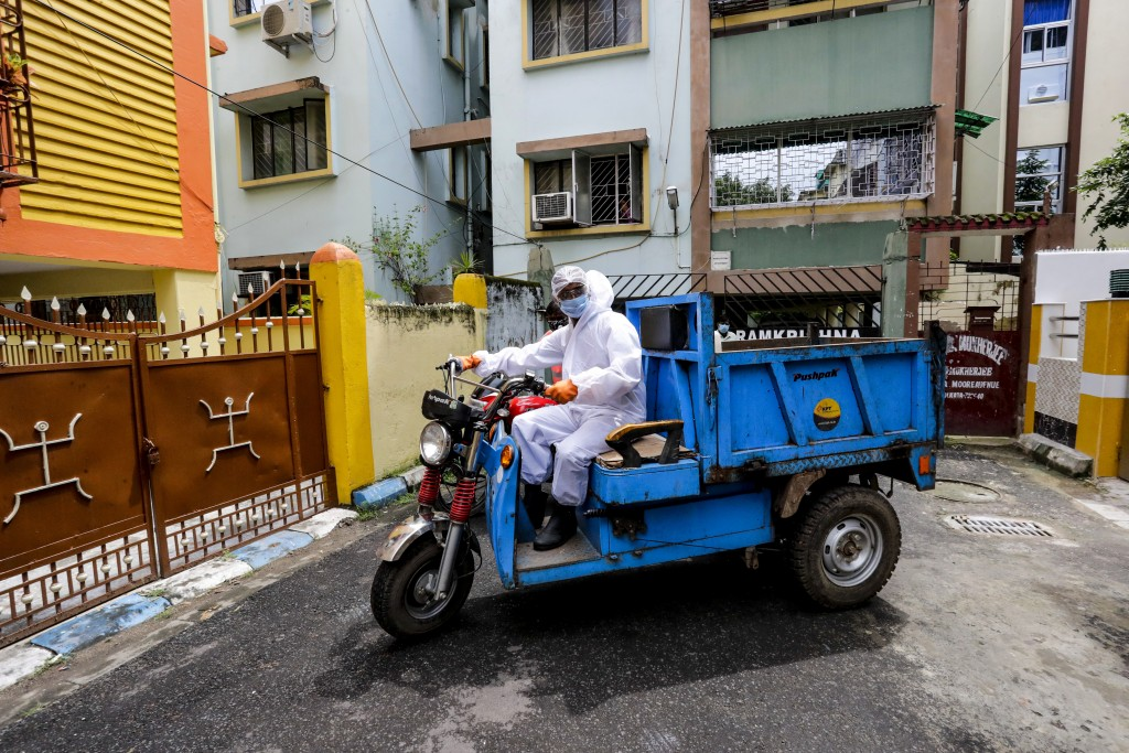 A civic staff in protective suit arrives to disinfect an apartment where one of the residents tested positive for COVID-19  in Kolkata, India, Tuesday...