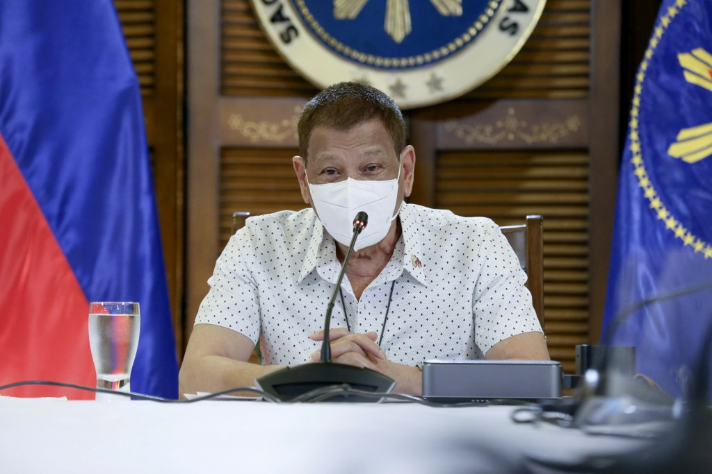 In this photo provided by the Malacanang Presidential Photographers Division, Philippine President Rodrigo Duterte wears a protective mask as he meets...
