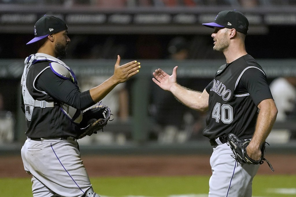 Colorado Rockies relief pitcher Tyler Kinley (40) is congratulated by catcher Elias Diaz after the final out of the ninth inning in a baseball game ag...
