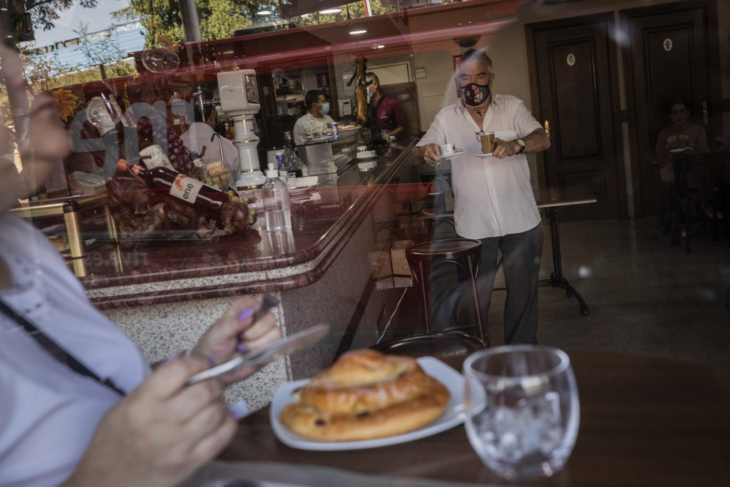 Customers have breakfast inside a bar in the southern neighbourhood of Vallecas in Madrid, Spain, Monday, Sept. 21, 2020. Police in the Spanish capita...