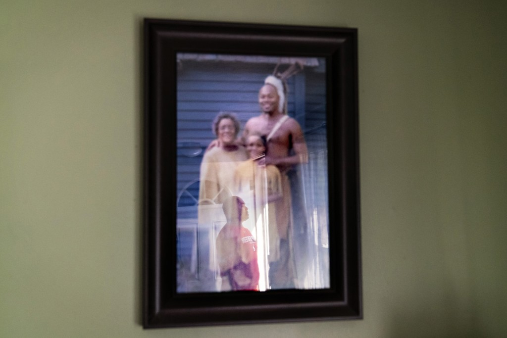 Troy Currence is reflected in a photo of himself with his mother, Hazel Harding Currence, left, and his daughter, Kendall Currence, three generations ...