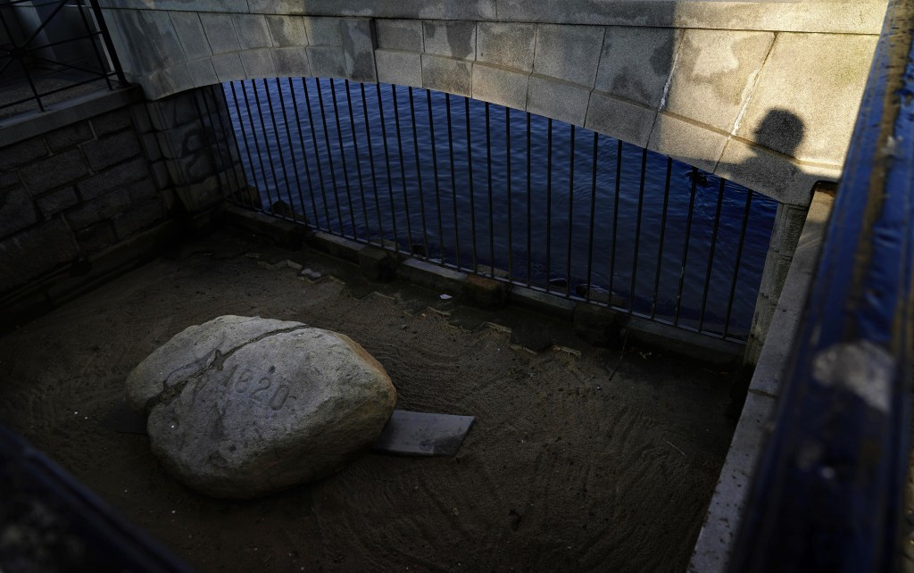 A visitor casts a shadow while looking at Plymouth Rock, the traditional point of arrival of the Pilgrims on the Mayflower in 1620, in Plymouth, Mass....