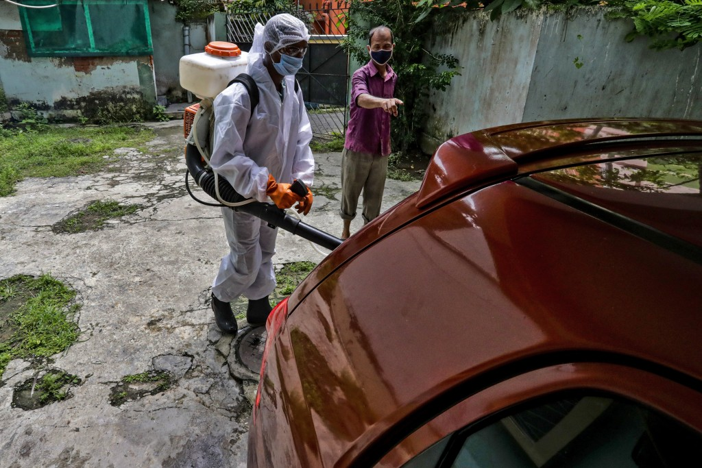 A civic staff in protective suit disinfects the parking area of an apartment where one of the residents tested positive for COVID-19 in Kolkata, India...